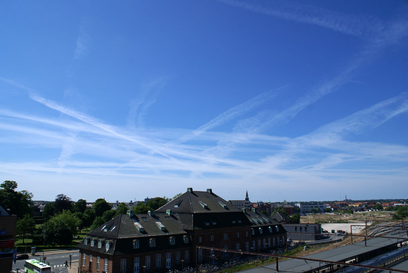 Aircraft contrails crisscrossing the sky above Odense city