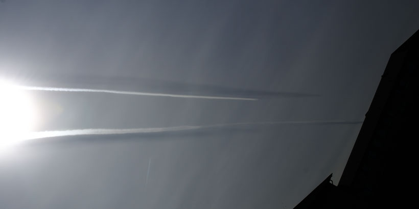 Persistent aircraft contrails making shadows in the sky